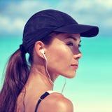 De vrouw die van de geschiktheidsagent aan muziek op strand luisteren stock foto