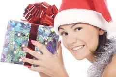 De vrouw die van de kerstman gift toont die de hoed van de Kerstman draagt. Stock Afbeeldingen