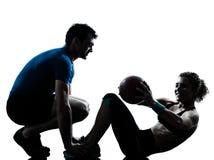 De vrouw die van de man de geschiktheidsbal uitoefent van de gewichtentraining Stock Afbeeldingen