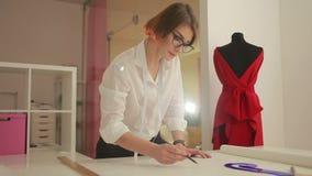De vrouw die van de manierontwerper thuis studio werken Naaister die kleren maken stock video