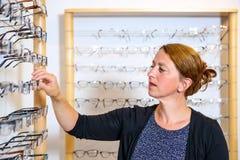 In de vrouw die van de opticienwinkel nieuwe glazen selecteren Stock Fotografie