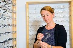 In de vrouw die van de opticienwinkel nieuwe glazen selecteren Stock Foto