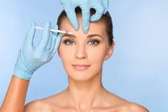 De vrouw die van de schoonheid botox injecties geeft stock foto