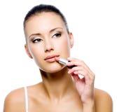 De vrouw die van de schoonheid lippenstift toepast Stock Fotografie