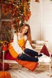 De vrouw die van de schoonheidsherfst op de portiek van geel en oranje Au glimlachen stock foto's