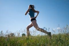 De vrouw die van de sport over groene gras en hemel loopt Stock Foto's