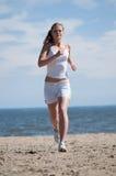 De vrouw die van de sport in overzeese kust loopt Royalty-vrije Stock Foto