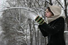 De vrouw die van de winter een sneeuw blaast Royalty-vrije Stock Foto's