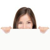 De vrouw die van het aanplakbord over teken kijkt Stock Foto's