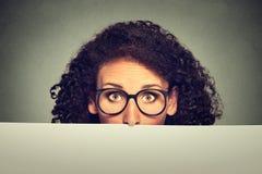 De vrouw die van het bannerteken in glazen over rand van leeg leeg document aanplakbord gluren Stock Afbeeldingen