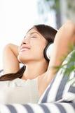 De vrouw die van hoofdtelefoons aan muziek luistert Stock Afbeeldingen