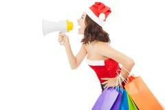 De vrouw die van Kerstmissanta een megafoon met giftzakken met behulp van Stock Foto