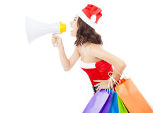 De vrouw die van Kerstmissanta een megafoon met giftzakken met behulp van Royalty-vrije Stock Afbeeldingen