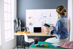 De vrouw die van de manierontwerper aan haar ontwerpen in de studio werken Stock Foto