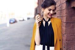 De vrouw die van de portretmanier op straat lopen Zij draagt geel jasje, glimlachend aan kant stock foto's