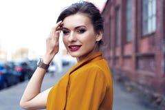 De vrouw die van de portretmanier op straat lopen Zij draagt geel jasje, glimlachend aan kant royalty-vrije stock foto