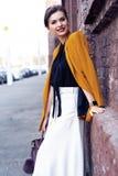De vrouw die van de portretmanier op straat lopen Zij draagt geel jasje, glimlachend aan kant stock foto