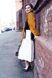 De vrouw die van de portretmanier op straat lopen Zij draagt geel jasje, glimlachend aan kant stock afbeelding