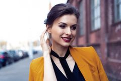 De vrouw die van de portretmanier op straat lopen Zij draagt geel jasje, glimlachend aan kant royalty-vrije stock afbeeldingen