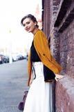 De vrouw die van de portretmanier op straat lopen Zij draagt geel jasje, glimlachend aan kant royalty-vrije stock foto's