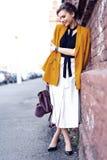 De vrouw die van de portretmanier op straat lopen Zij draagt geel jasje, glimlachend aan kant stock afbeeldingen