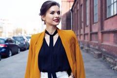 De vrouw die van de portretmanier op straat lopen Zij draagt geel jasje, glimlachend aan kant royalty-vrije stock afbeelding