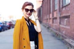 De vrouw die van de portretmanier in zonnebril op straat lopen Zij draagt geel jasje, glimlachend aan kant stock afbeeldingen