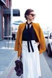 De vrouw die van de portretmanier in zonnebril op straat lopen Zij draagt geel jasje, glimlachend aan kant royalty-vrije stock afbeelding