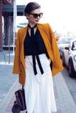 De vrouw die van de portretmanier in zonnebril op straat lopen Zij draagt geel jasje, glimlachend aan kant royalty-vrije stock afbeeldingen