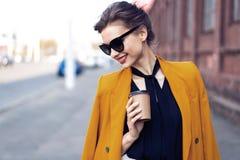De vrouw die van de portretmanier in zonnebril op straat lopen Zij draagt geel jasje, glimlachend aan kant royalty-vrije stock foto's