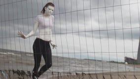 De vrouw die van de prestatieskunstenaar in witte verf op overzeese kust langs metaalomheining lopen stock videobeelden