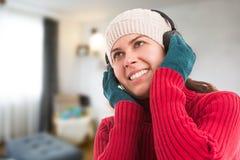 De vrouw die de winter dragen kleedt binnen het luisteren muziek Royalty-vrije Stock Foto