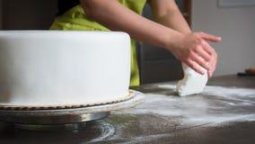 De vrouw die wit fondantje voor cake voorbereiden die, handen detailleert, concentreert zich op de cake verfraaien stock afbeelding