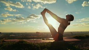 De vrouw die yoga in drijvende boot doen stelt in het park bij zonsondergang stock footage
