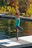 De vrouw die yoga in openlucht in boom doet stelt dichtbij water Stock Afbeeldingen