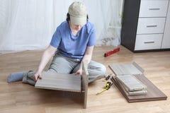 De vrouw die zelfassemblagemeubilair samenbrengen assembleert vlak-pac-vlakte royalty-vrije stock afbeelding