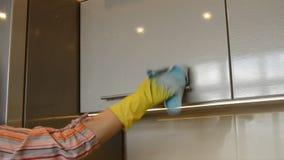 De vrouw dient een gele rubberhandschoen met een doek in schoonmaakt de oppervlakte van de ijskast en de keukenkast gebruikend de stock footage