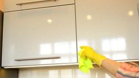 De vrouw dient een gele rubberhandschoen in schoonmaakt de glanzende oppervlakte van een moderne plastic keukenkast met een doek  stock video