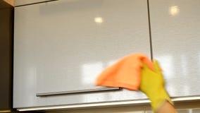 De vrouw dient een gele rubberhandschoen in schoonmaakt de oppervlakte van een moderne plastic keukenkast met een oranje doek Het stock videobeelden