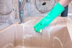 De vrouw dient een handschoen in schoonmaakt een keukengootsteen royalty-vrije stock foto