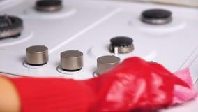 De vrouw dient het rode rubber vuile gasfornuis van handschoenenwassen met een borstel en een spons in stock videobeelden