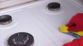 De vrouw dient het rode rubber vuile gasfornuis van handschoenenwassen met een borstel en een spons in stock video