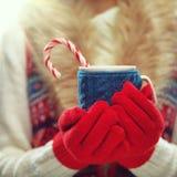 De vrouw dient wollen rode handschoenen in houdend comfortabele mok met hete cacao, thee of koffie en suikergoedriet De winter en Stock Afbeelding