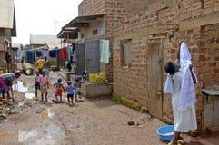 De vrouw doet de wasserij terwijl de kinderen in neighborhoo stock fotografie
