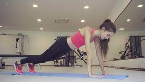 De vrouw doet plank als deel van dwarsgeschiktheid, Bodybuilding-gymnastiek opleidingsroutine stock videobeelden