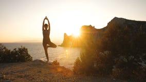 De vrouw doet yoga bij zonsondergang