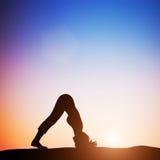 De vrouw in dolfijnyoga stelt het mediteren bij zonsondergang zen Royalty-vrije Stock Afbeeldingen