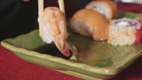 De vrouw dompelt sushi met garnalen in saus met eetstokjes bij Japans restaurant onder stock videobeelden