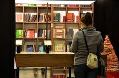 De vrouw doorbladert boeken bij boekhandel Stock Foto