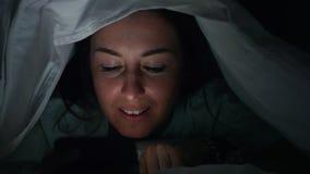 De vrouw doorbladert sociale media in mobiele telefoon bij nacht onder de deken, Gezichtsclose-up stock footage
